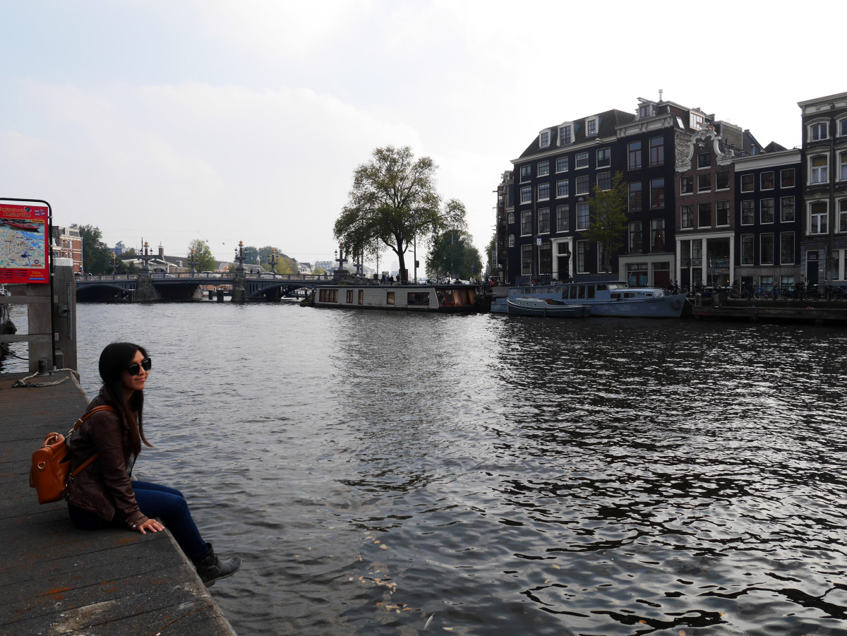 Me sitting by the peaceful canal in Amsterdam, Netherlands| Laugh Travel Eat