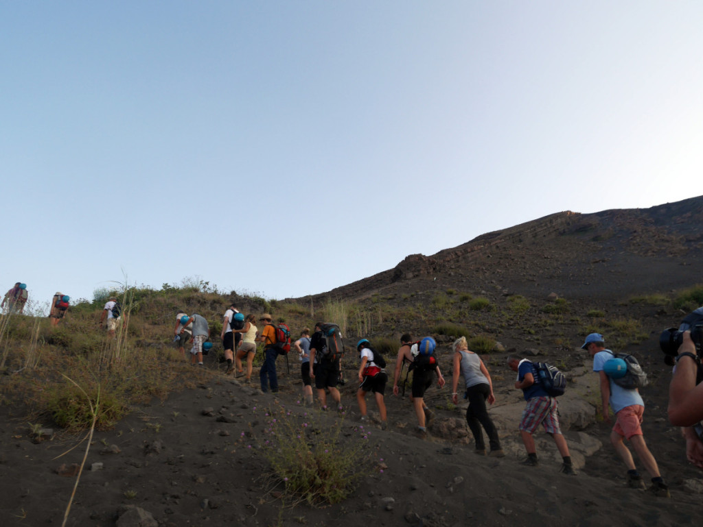 A long line of people hiking up Stromboli volcano in the evening light