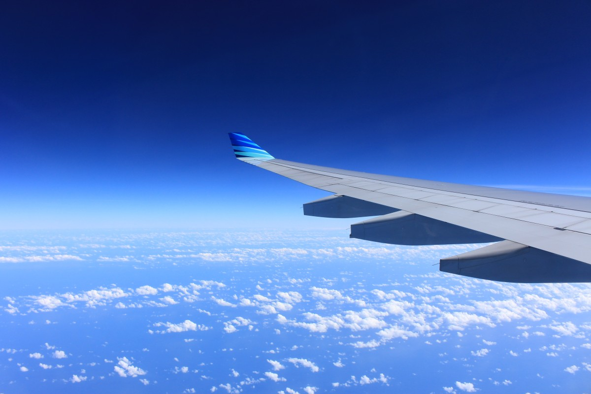 Looking out at the sky and airplane wing mid-flight| Laugh Travel Eat