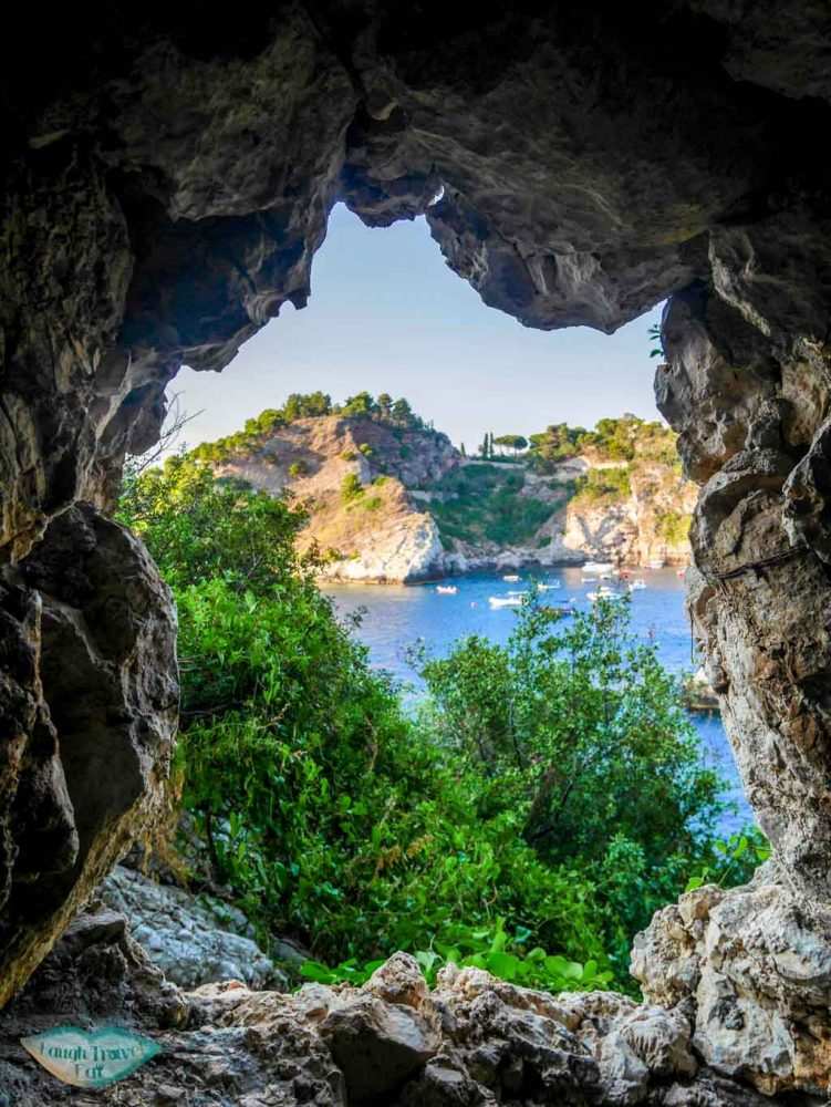 Peeking through a window through Isola Bella, Taormina | Laugh Travel Eat