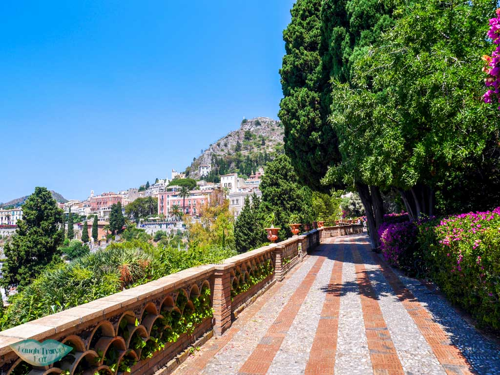 The beautiful public Garden of Villa Comunale in Taormina, Italy with a gorgeous view and colourful flowers | Laugh Travel Eat