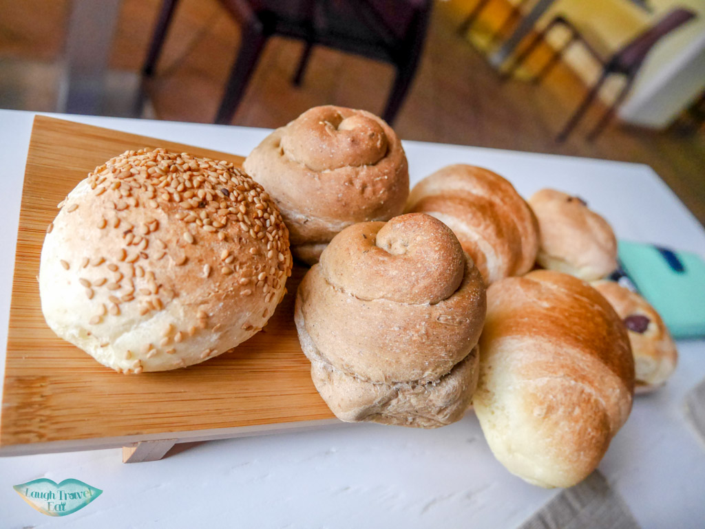 complimentary assorted bread plate on a wooden board at Flam Osteria in Palermo | Laugh Travel Eat