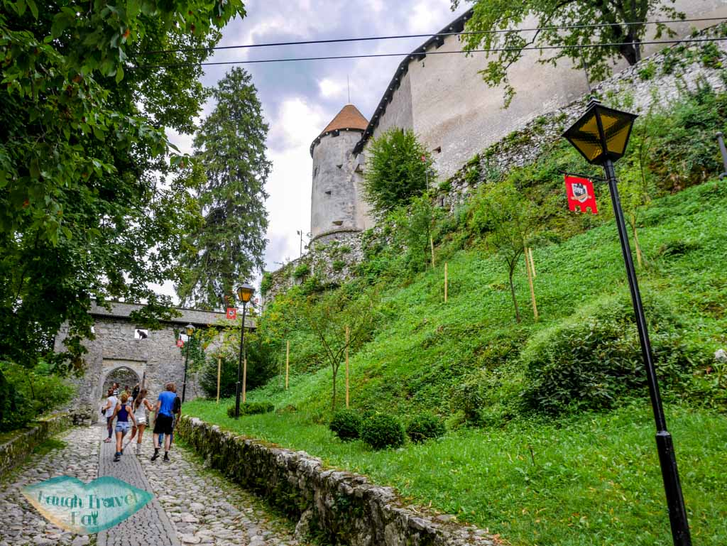 Cobble-stone-path-with-flags-on-lamppost-leading-to-Castle-Bled-Slovenia-laugh-travel-eat