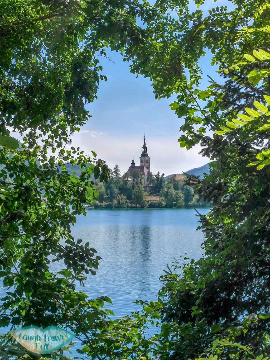 Bled island through trees at Bled | Laugh Travel Eat