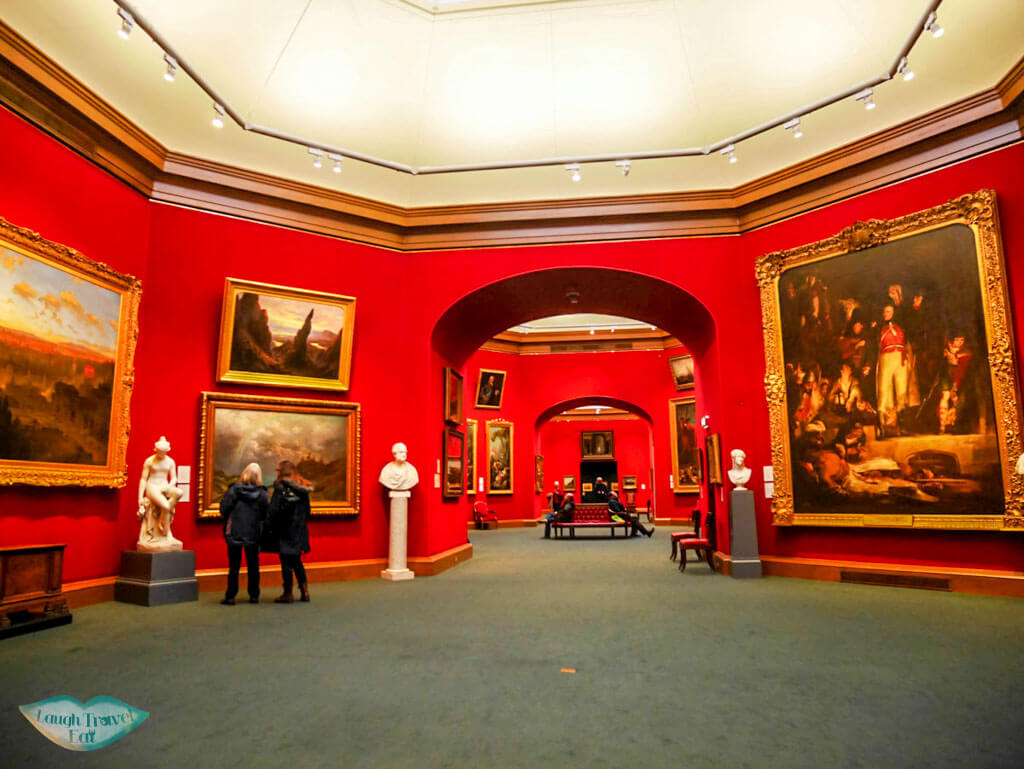Interior of Scottish National Gallery with red wallpaper and paintings in gold frame - Laugh Travel Eat