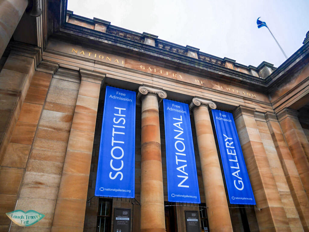 Neoclassical building with blue banners of the Scottish National Gallery - Laugh Travel Eat