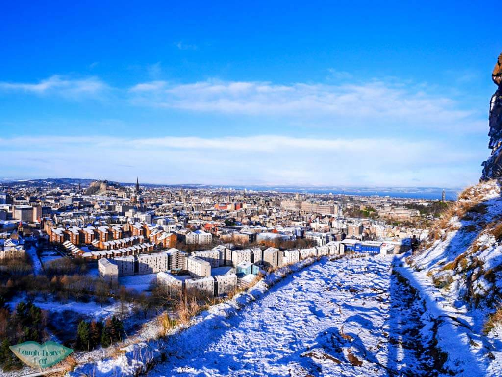 On the way down from Arthur's seat through the snow-covered path, with houses within site - Laugh Travel Eat