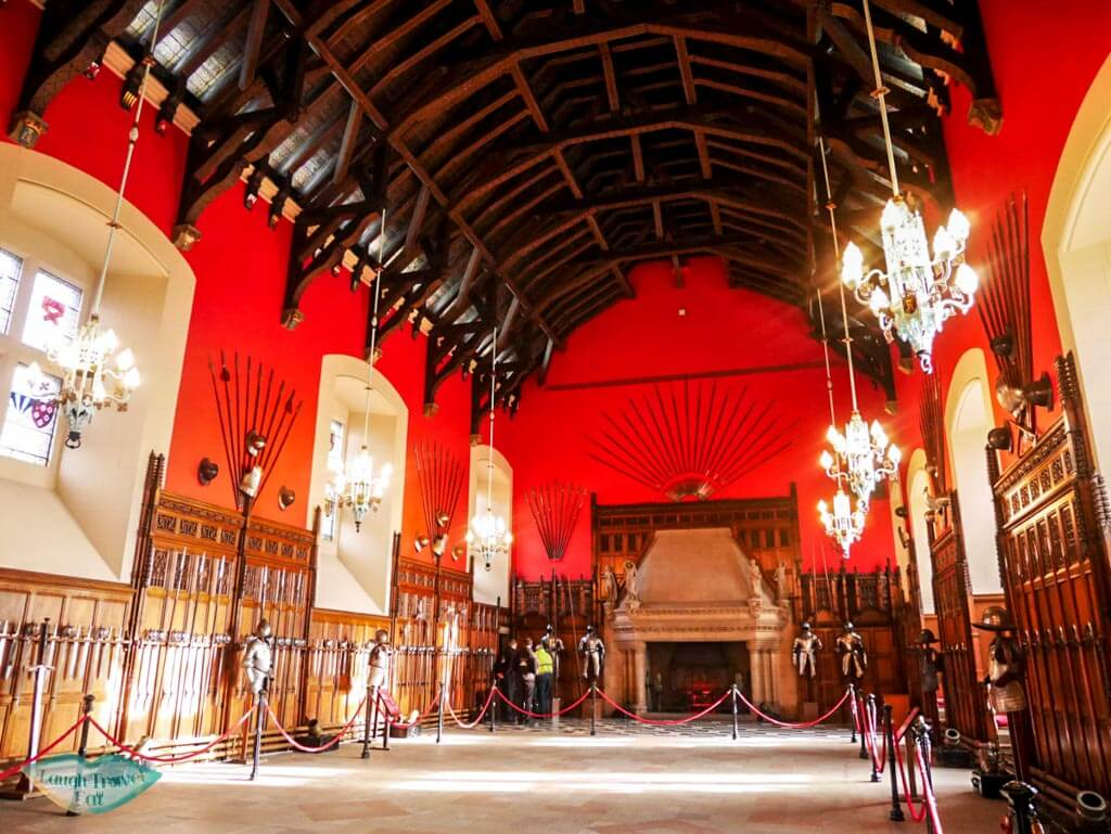 The banquet hall in the castle with red wall paper, wooden panels and a fire place edinburgh castle - Laugh Travel Eat