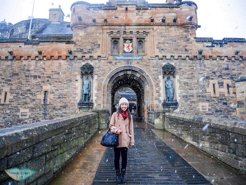 me posing in front of Edinburgh Castle in snow - Laugh Travel Eat