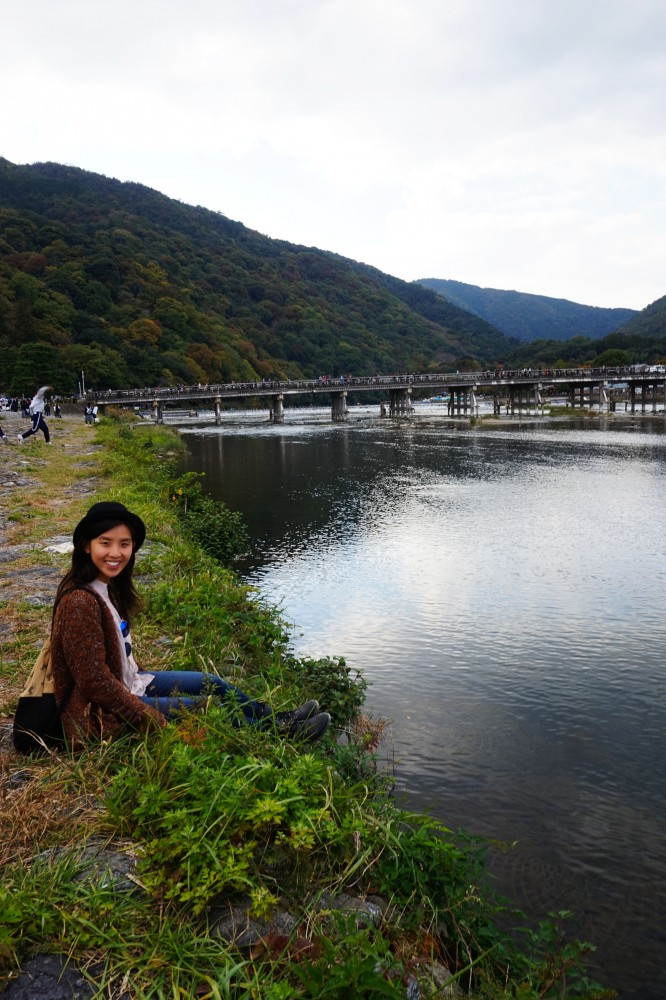 Posing along the bank of river in front of Togetsukyo Bridge in Arashiyama, Kyoto, Japan | Laugh Travel Eat