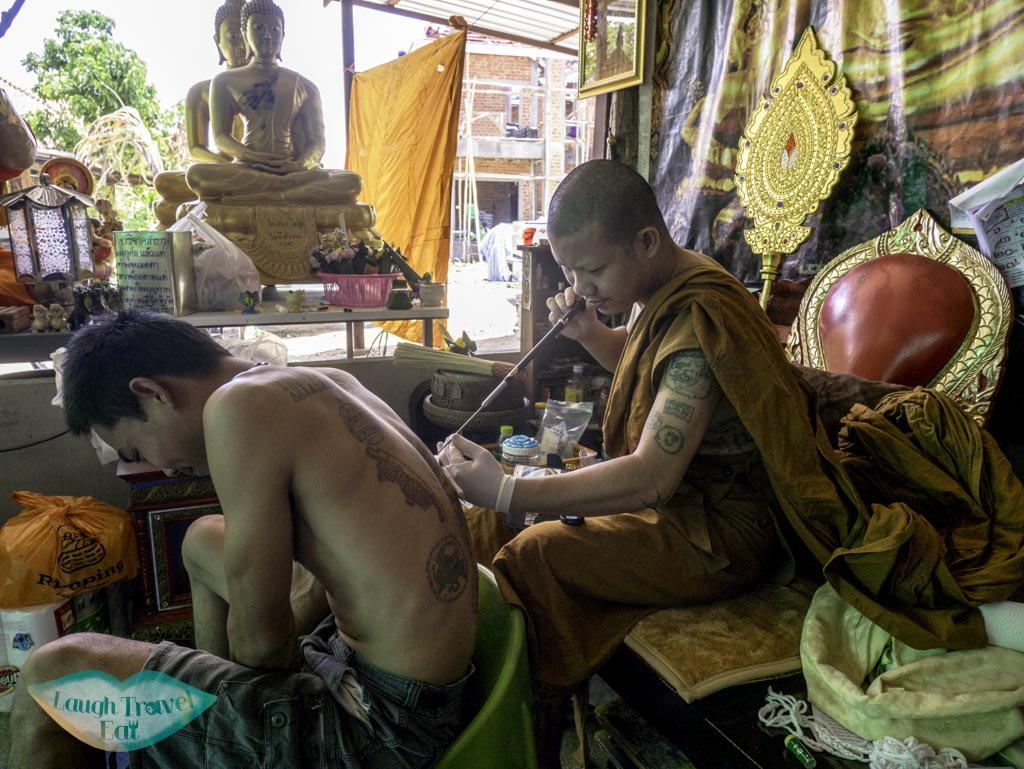 a-man-getting-a-sak-yang-tatto-chiang-mai-thailand-laugh-travel-eat