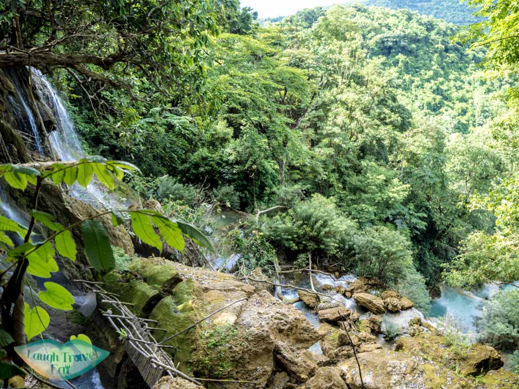 view of main waterfall from top kuang si waterfall luang prabang laos - laugh travel eat