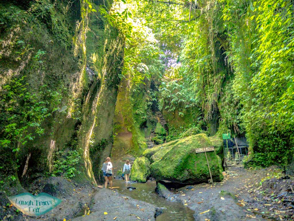 walking-through-canyon-tukad-cepung-waterfall-fees-bali-indonesia-laugh-travel-eat