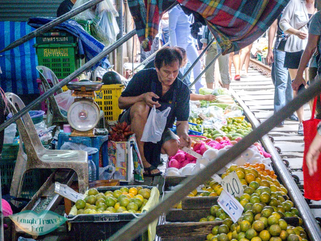 man-selling-fruitsmekong-railway-market-bangkok-thailand-laugh-travel-eat