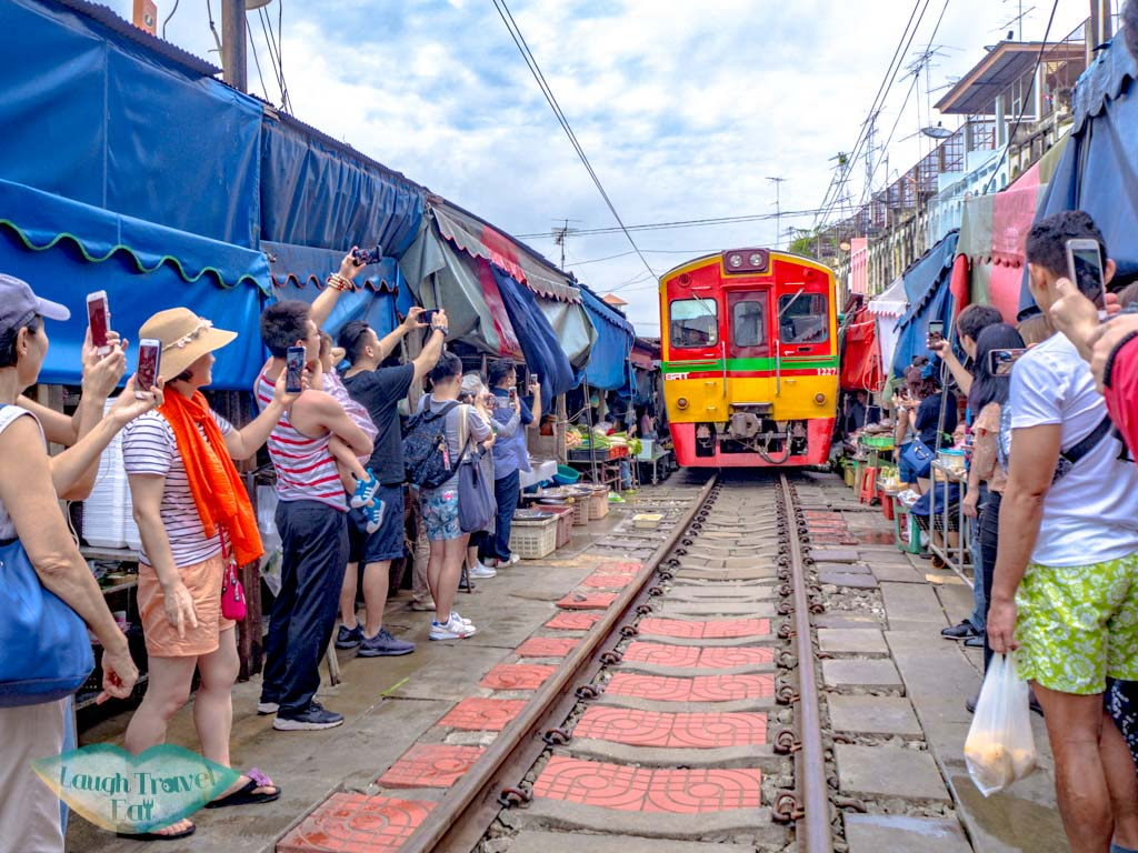 train-coming-in-at-mekong-railway-market-bangkok-thailand-laugh-travel-eat