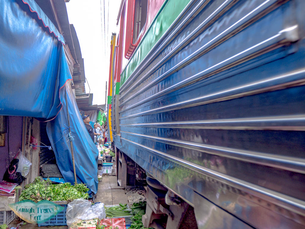 train-passing-maeklong-railway-market-bangkok-thailand-laugh-travel-eat