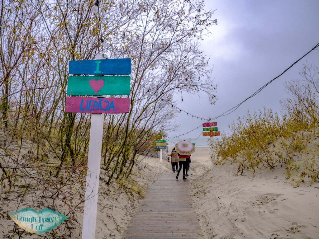 entry to the white sand beach liepaja latvia - laugh travel eat