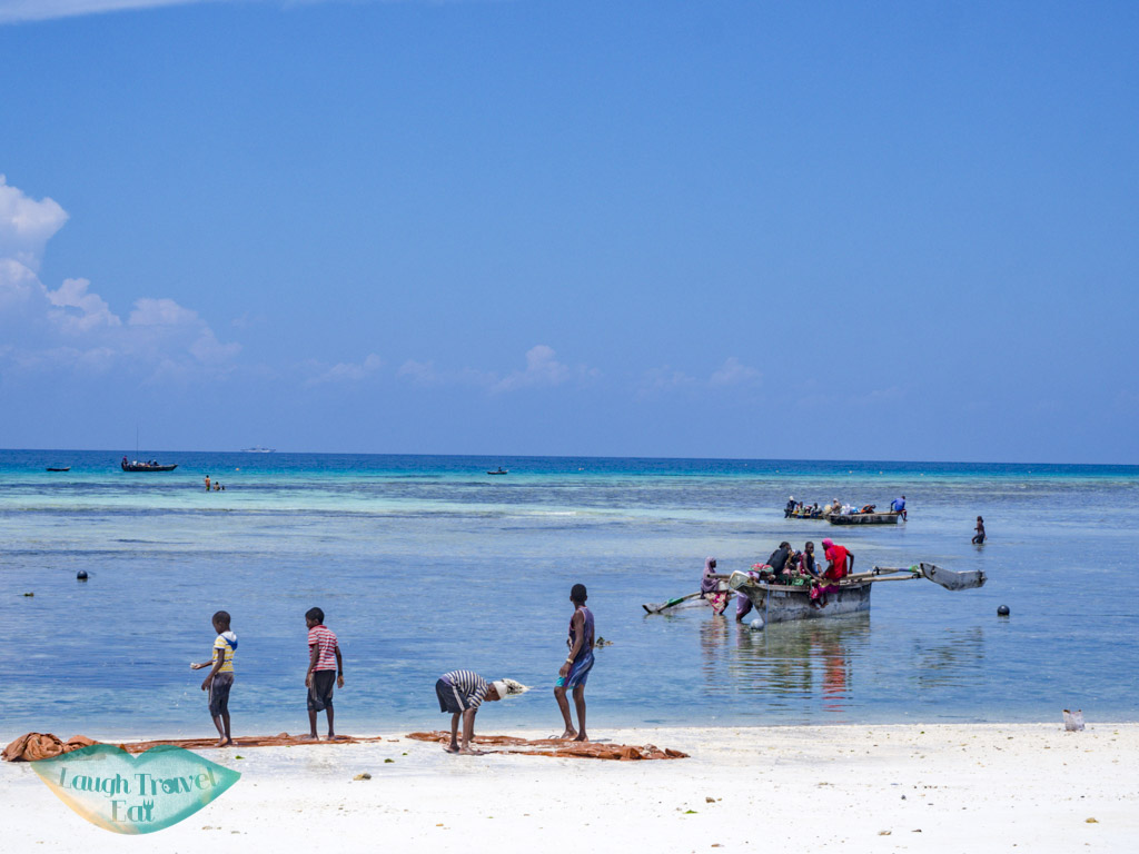 life on beach low tide nungwi zanzibar tanzania - laugh travel eat